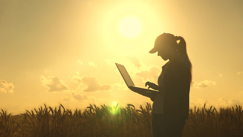 """An image of a woman holding a computer in front of a field for our article answering the question, """"Can I get an agriculture degree online?"""""""